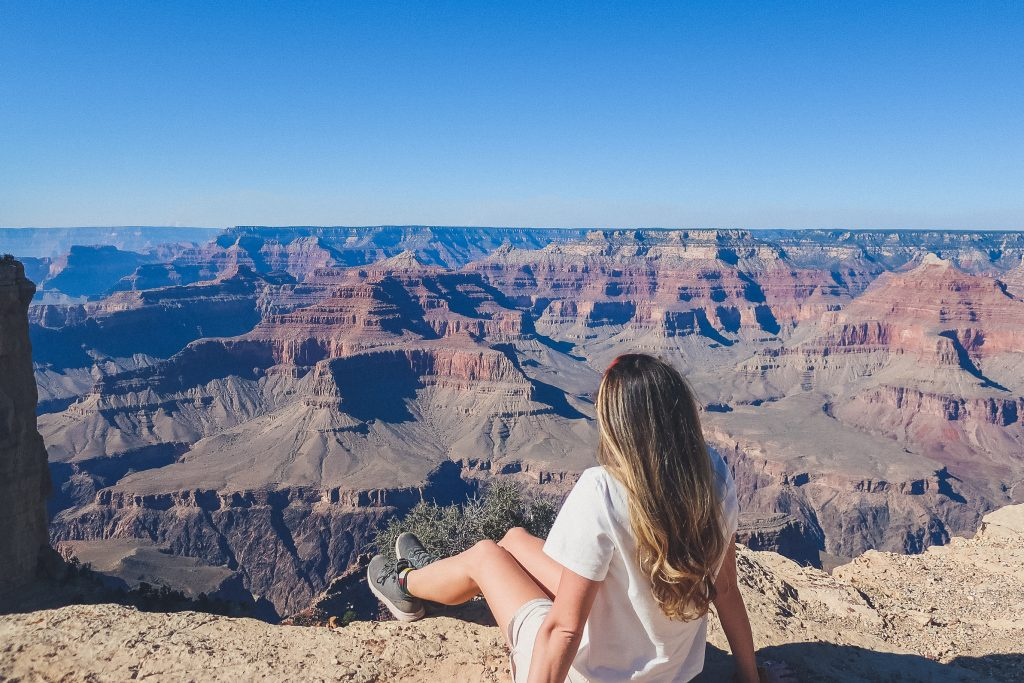 woman looks out on the grand canyon wearing tee and shorts