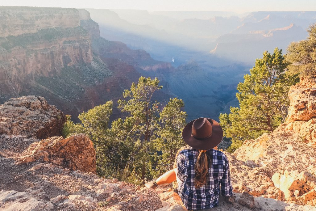 woman looks into Grand Canyon wearing felt fedora and plaid shirt