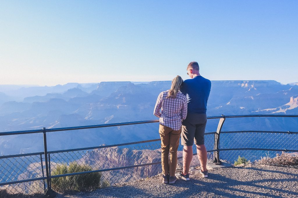woman wears cargo pants at the grand canyon, watches sunset with boyfriend