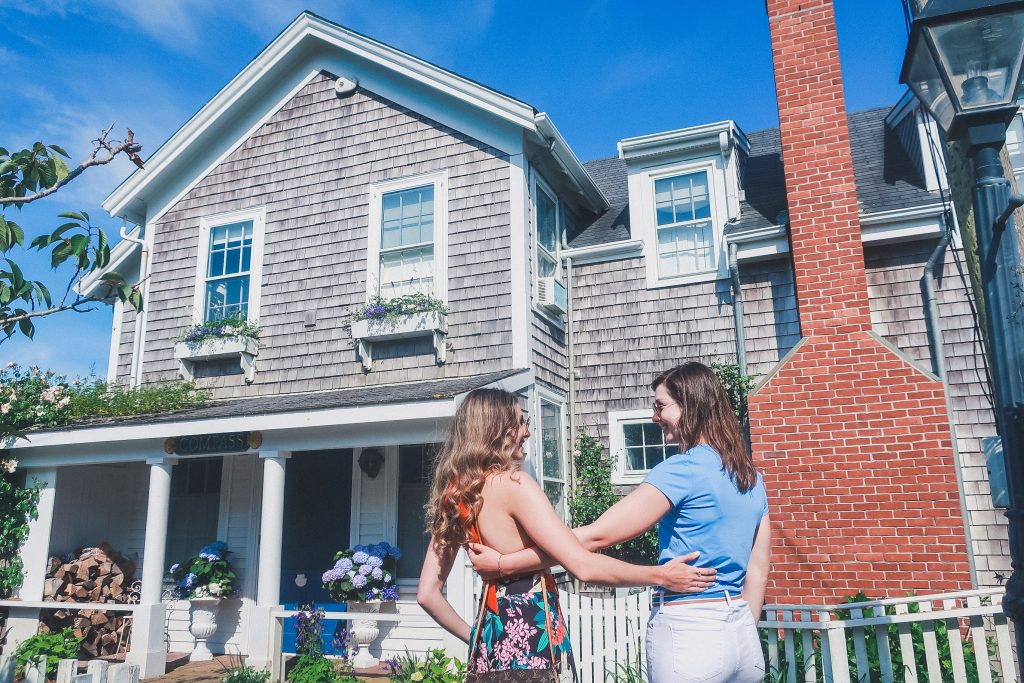 two woman walking around Sconset admiring beautiful cottages in nantucket