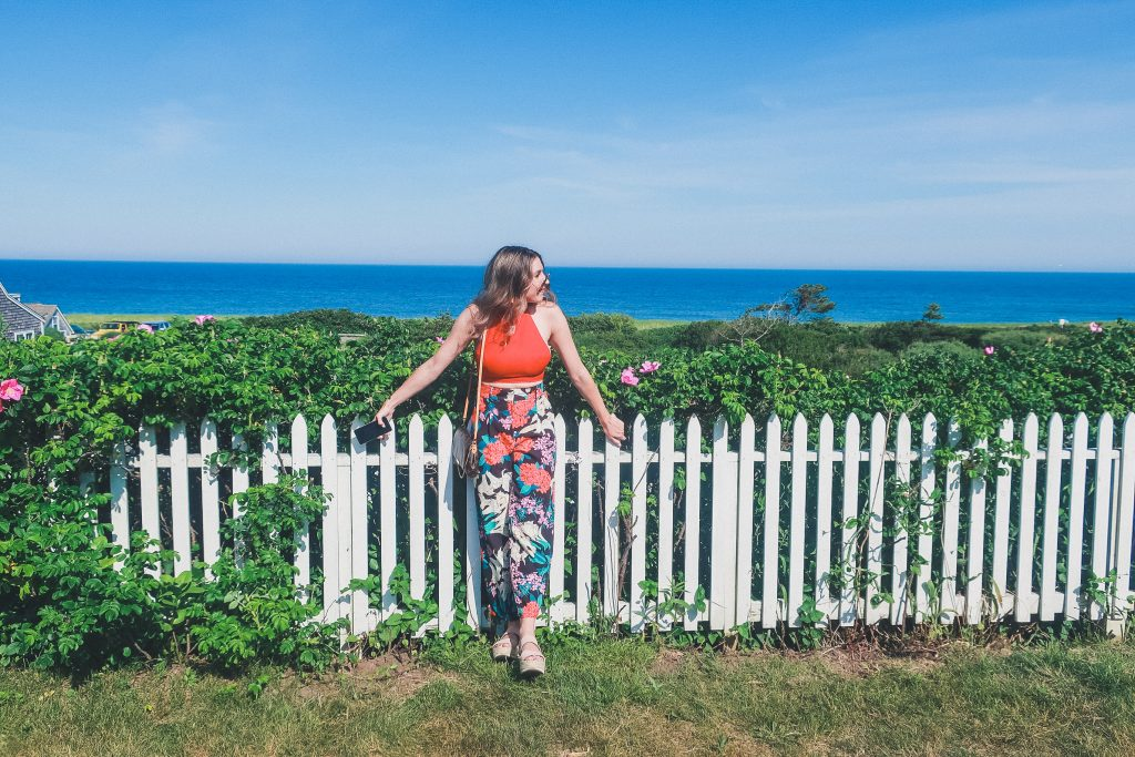 woman relaxes next to white picket fence near Sconset Bluff Walk on Nantucket