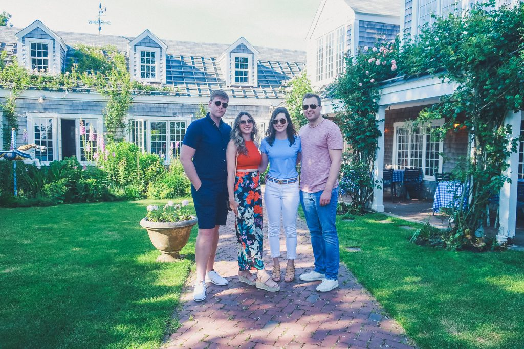 group of friends stands in garden of the The Chanticleer Nantucket