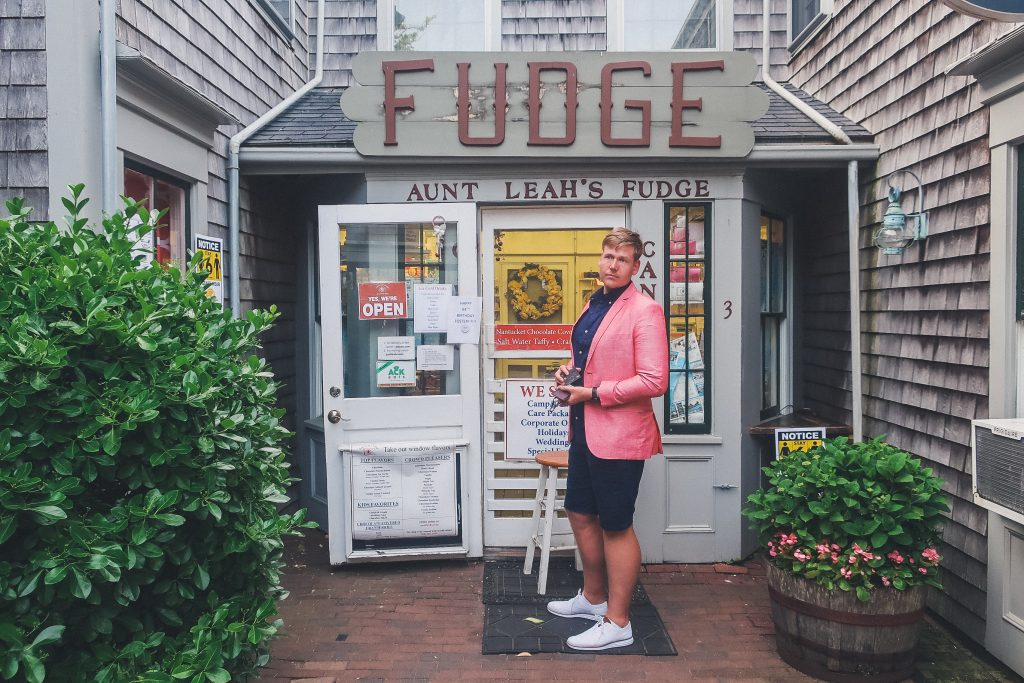 man stands outside aunt Leah's Fudge shop in Nantucket around sunset