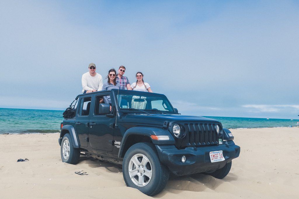 Madaket Beach, 4 friends pop out of the top of a black Jeep