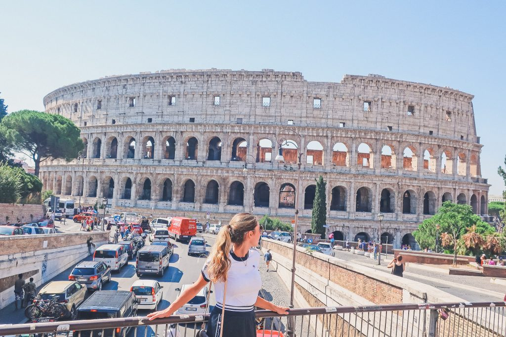 woman stands in front of the Colosseum