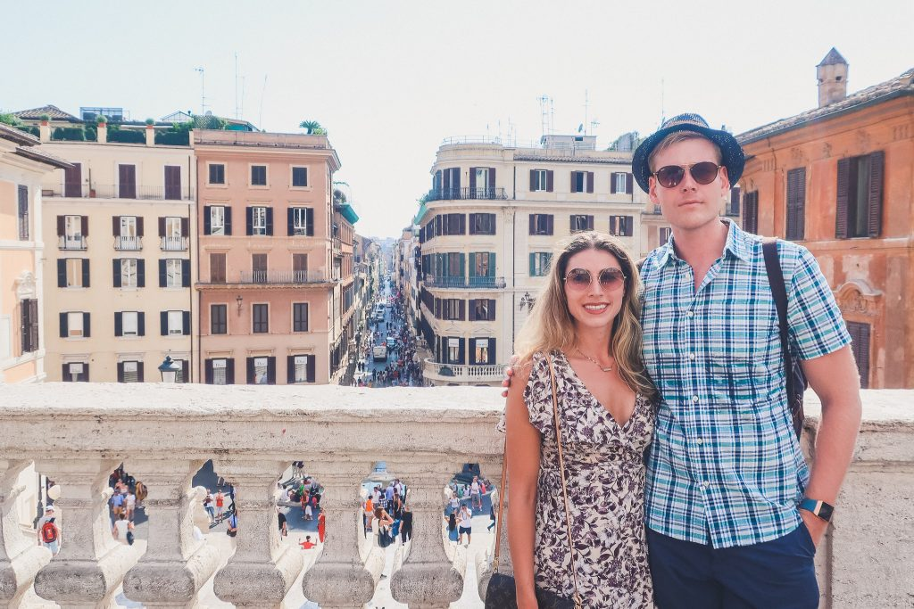 couple stands at spanish steps in rome
