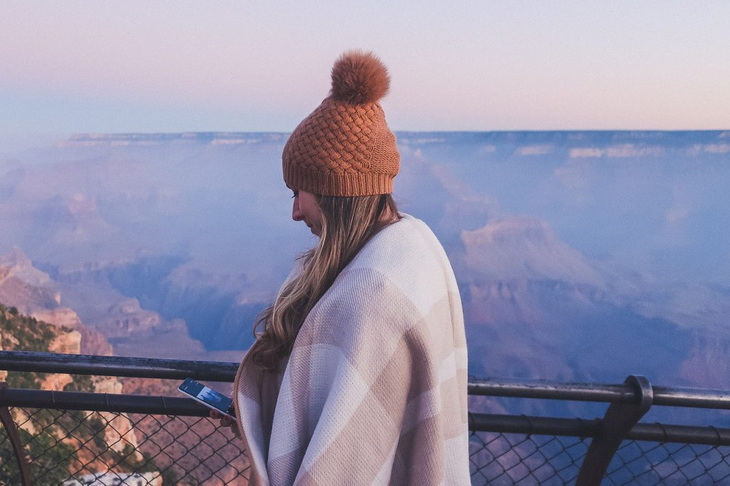 woman wears fur pom hat and grand canyon