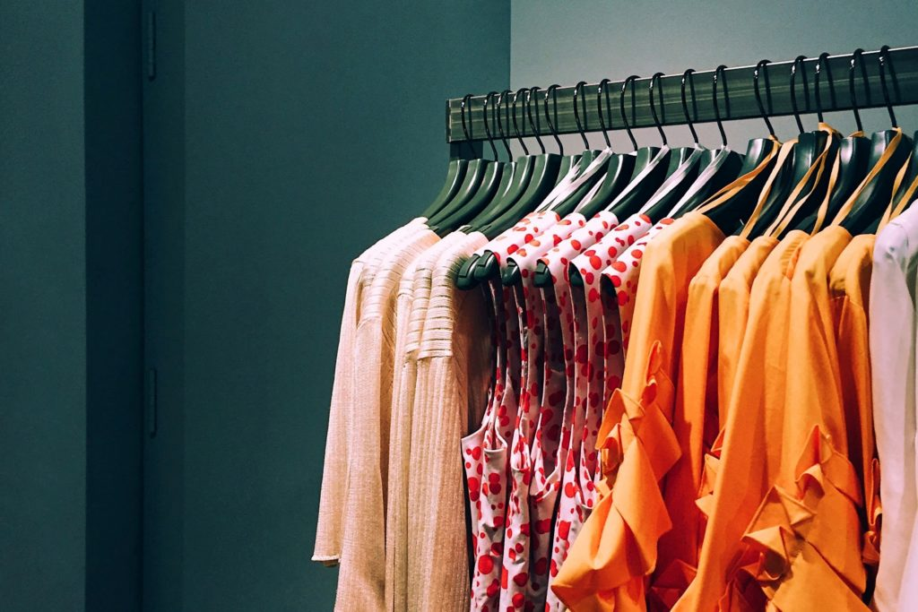 women's clothes, bright warm tones on clothing rack
