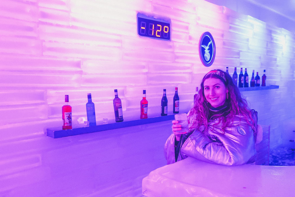 woman stands next to the thermometer at an Ice bar in El Calafate
