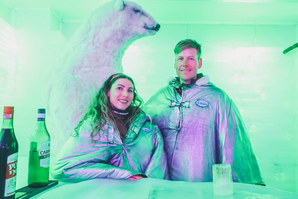couple stands next to polar bear at ice bar in el calafate