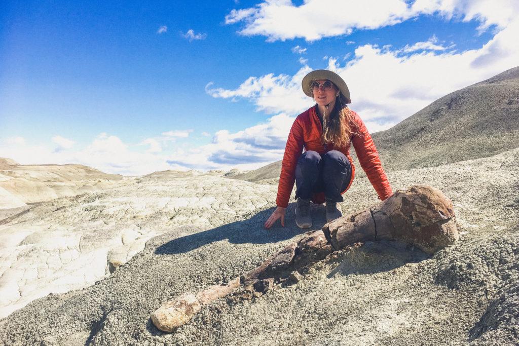 woman stands next to dinosaur femur fossil