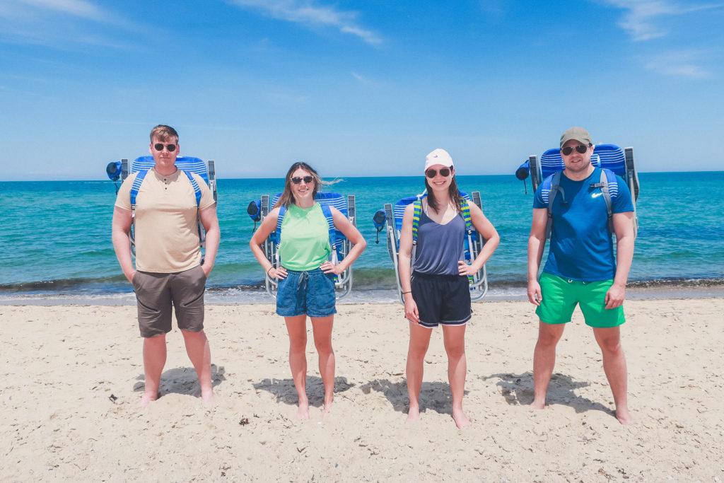 4 friends on a beach wearing backpack beach chairs