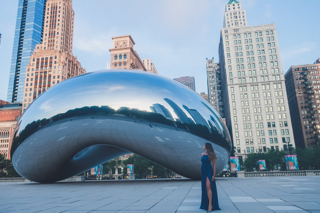 woman stands near the bean at dusk in chicago